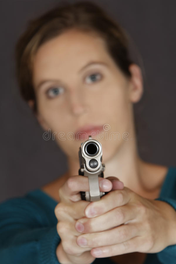 Kaukasische Frau, die unter Verwendung einer Pistole sich verteidigt stockfoto