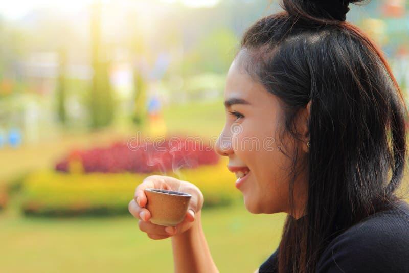 Kaukasische Frau entspannen sich mit trinkendem Tee am Balkonhaus am Morgen, lächelndes Glück des Mädchens mit heißem Getränk lizenzfreies stockfoto