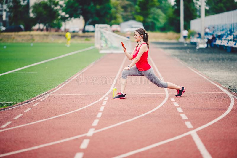 Kaukasische Frauen der Sporteignung, die Aufwärmen vor Übung tun Athlet, der die Beine tun Aufwärmen vor der Ausbildung ausdehnt stockbilder