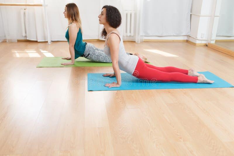 Kaukasische Frauen, die Kobra asana im Yogaverein tuend ausarbeiten lizenzfreie stockfotos