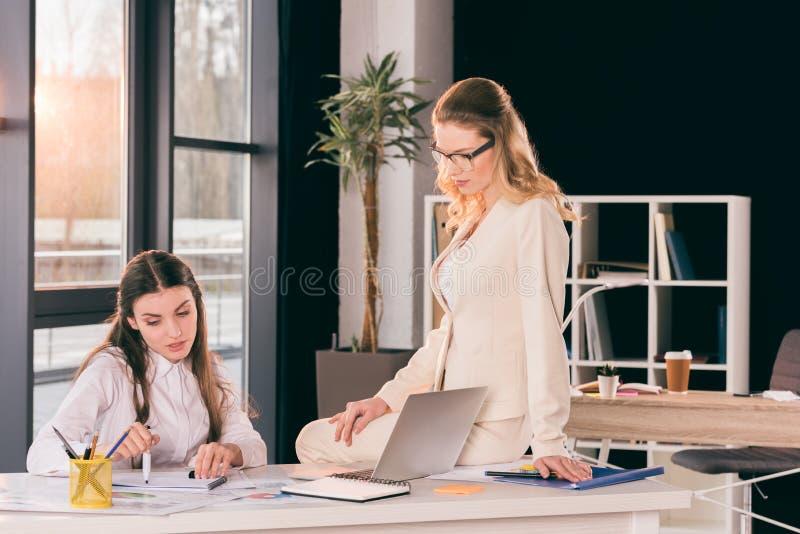 Kaukasische Geschäftsfrauen im formalwear sprechend beim Arbeiten im modernen Büro lizenzfreie stockfotos