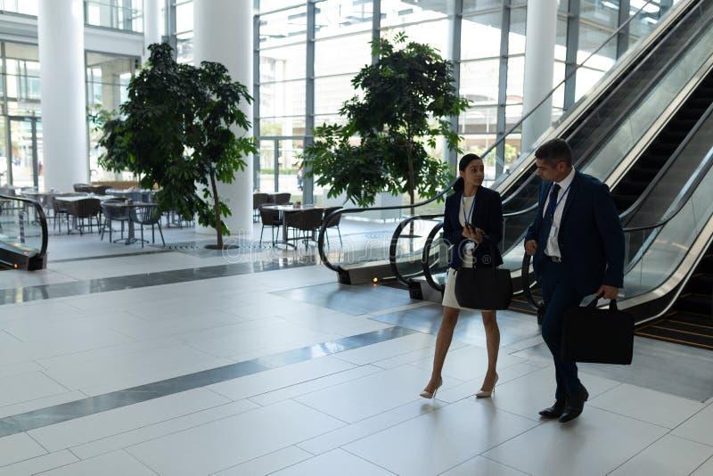 Kaukasische Geschäftsmann- und Mischrassegeschäftsfrau, die auf einander beim nach unten an sich bewegen einwirkt stockfoto