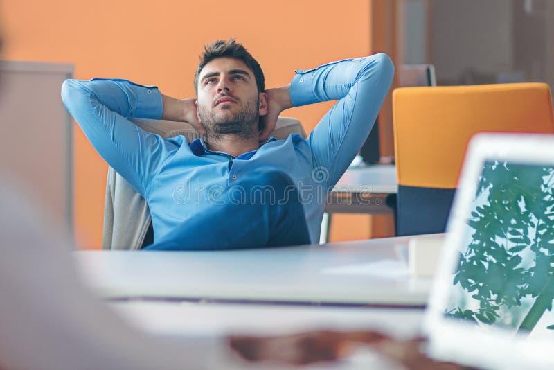 Kaukasische Geschäftsperson, die in denkenden träumenden Händen des Büros hinter Kopf sitzt lizenzfreie stockbilder