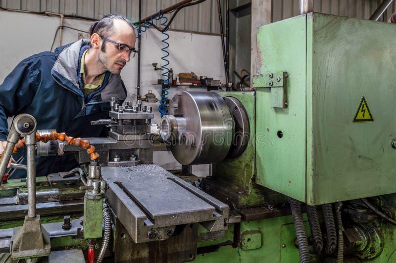 Kaukasische ingenieur die op het asblok van het draaien van draaibankmachine letten in fabriek stock foto