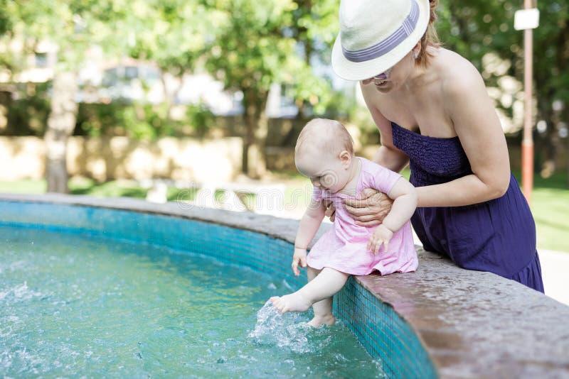Kaukasische jonge de babydochter van de vrouwenholding terwijl zij aan kant van fontein en bengelende benen zit stock afbeeldingen