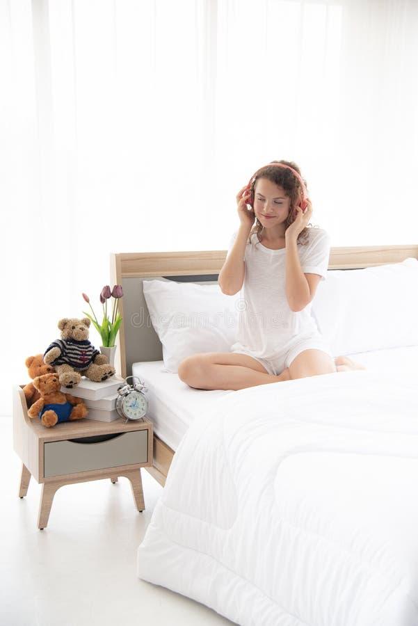 Kaukasische jonge en mooie gelukkige vrouw met het zitten op het comfortabele tweepersoonsbed in de moderne of minimale binnenlan stock afbeelding