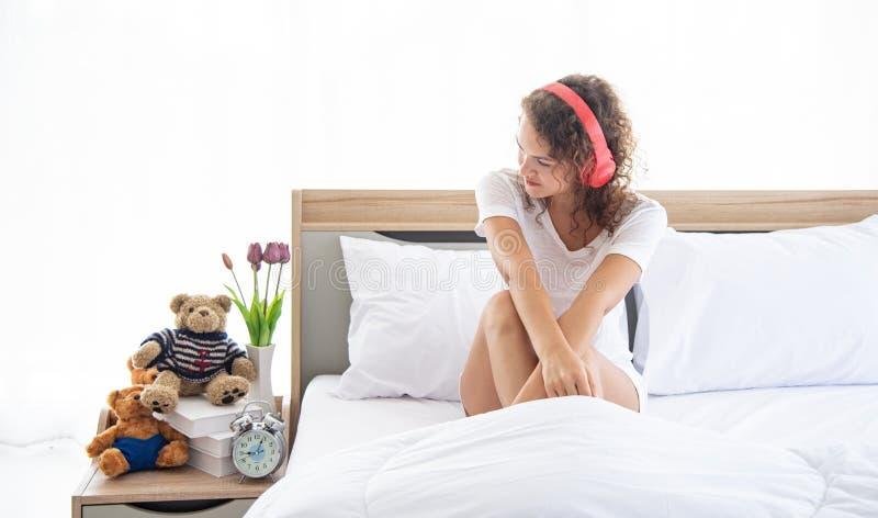 Kaukasische jonge en mooie gelukkige vrouw met hoofdtelefoonzitting op het comfortabele tweepersoonsbed in de moderne slaapkamer stock fotografie