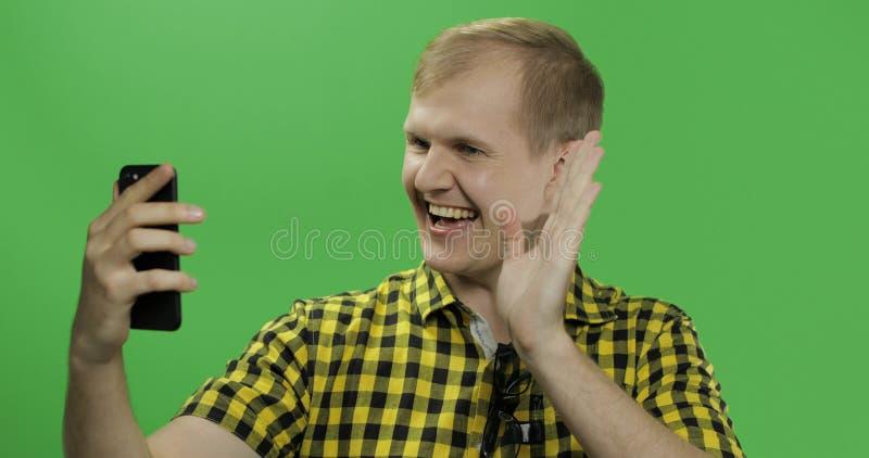Kaukasische jonge mens in geel overhemd die mobiele telefoon voor videogesprek met behulp van royalty-vrije stock afbeeldingen