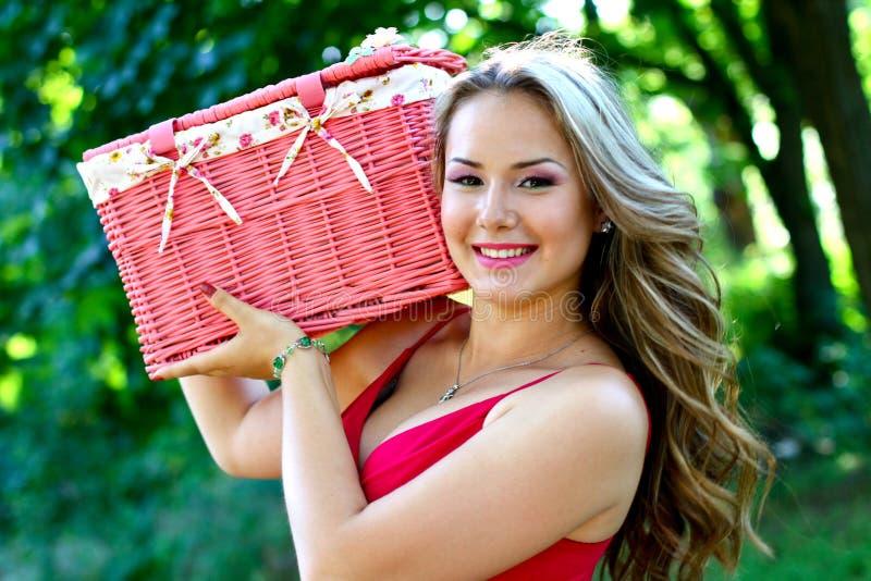 Kaukasische jonge vrouw met roze uitstekende mand stock afbeelding