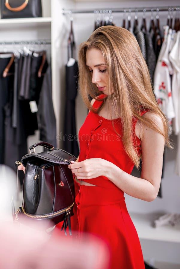 Kaukasische jonge vrouwelijke klant die leerrugzak kiezen van nieuwe vrouwens inzameling stock afbeeldingen