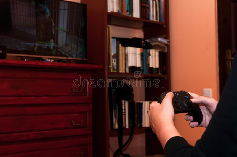 Kaukasische jongen die op Xbox Één videospelletje spelen stock foto