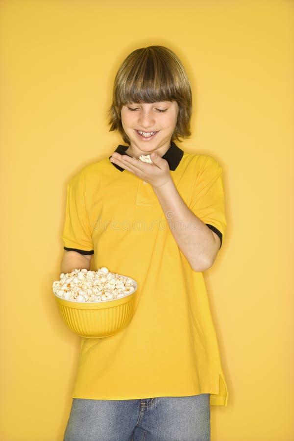 Kaukasische jongen met kom popcorn. stock fotografie