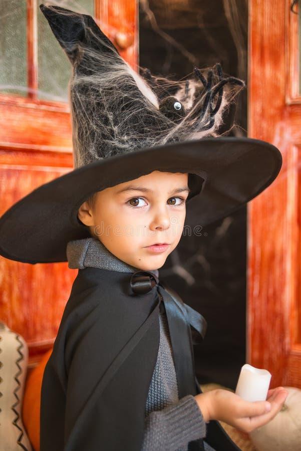 Kaukasische jongen in van het de tovenaarskostuum van farytalecarnaval de holdingskaars royalty-vrije stock foto