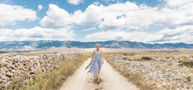 Kaukasische junge Frau im Sommerkleiderholdingblumenstrauß von Lavendelblumen beim Gehen im Freien durch trockenes felsiges stockfotos