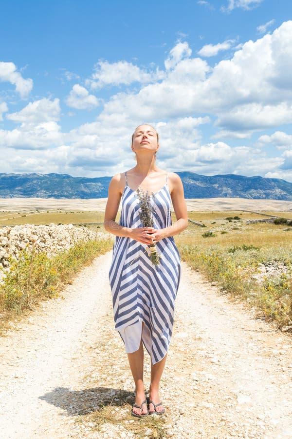 Kaukasische junge Frau im Sommerkleiderholdingblumenstrauß von Lavendelblumen reine Mittelmeernatur an felsigem genießend lizenzfreies stockbild