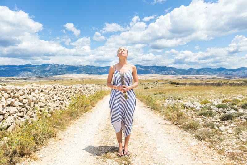 Kaukasische junge Frau im Sommerkleiderholdingblumenstrauß von Lavendelblumen reine Mittelmeernatur an felsigem genießend lizenzfreies stockfoto