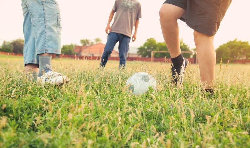 Kaukasische Jungen mit einem Fußball auf einem Fußballplatz stockbilder