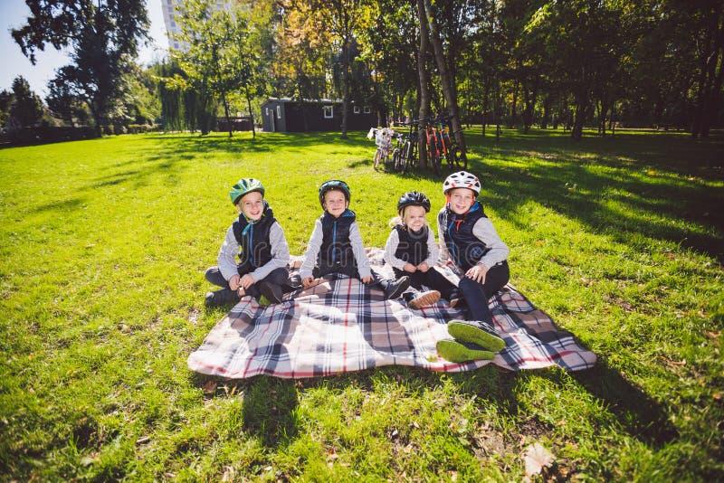 Kaukasische Kinder der großen Familie Drei Brüder und sitzendes Stillstehen der Schwester auf Decke außerhalb des Parks Gr lizenzfreies stockbild