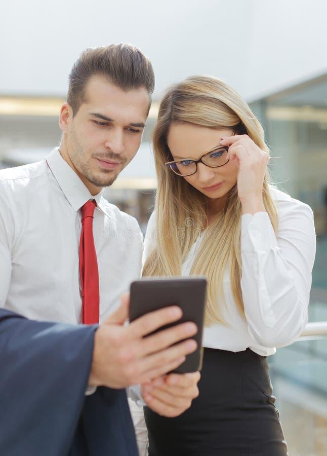 Kaukasische lesende schlechte Nachrichten des Geschäftsmannes und der Geschäftsfrau auf digi lizenzfreies stockbild