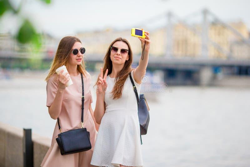 Kaukasische Mädchen, die selfie Hintergrund große Brücke herstellen Junge touristische Freunde, die auf draußen lächeln der Feier lizenzfreie stockfotos