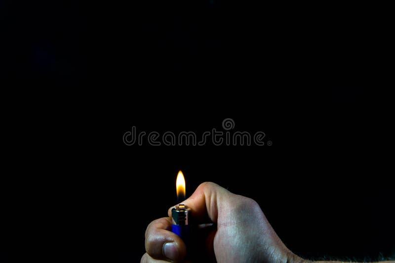 Kaukasische männliche Hand, die ein Feuerzeug hält lizenzfreies stockbild