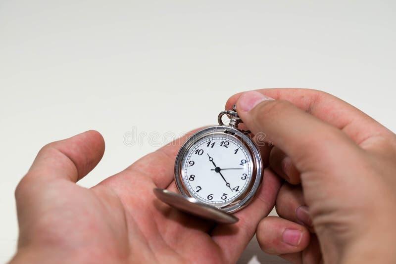 Kaukasische männliche Hand, welche die Taschenuhr justiert stockbild
