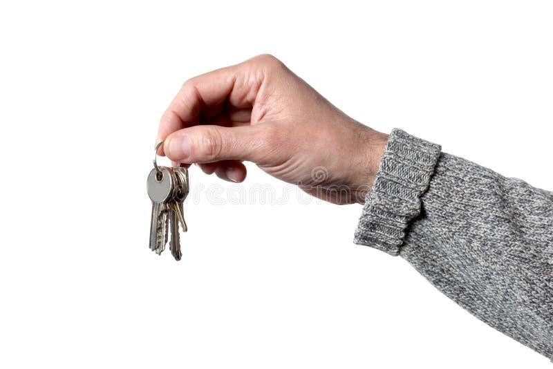 Kaukasische Mann ` s Hand, die Schlüssel lokalisiert auf weißem Hintergrund mit Beschneidungspfad hält lizenzfreie stockfotos