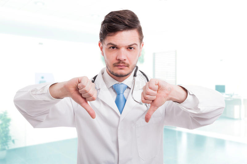 Kaukasische mannelijke arts die dubbele duim benedenteken tonen royalty-vrije stock foto