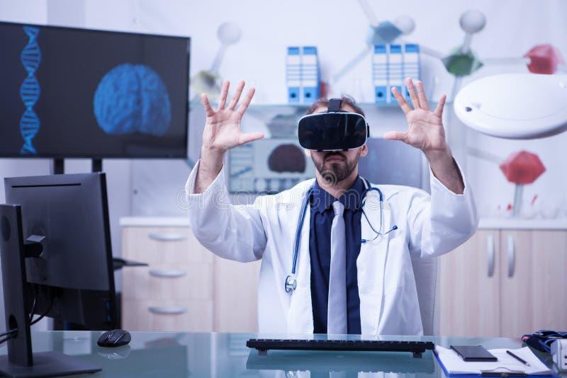 Kaukasische mannelijke arts die virtuele werkelijkheidsglazen dragen die geduldige resultaten testen stock afbeeldingen