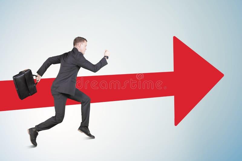 Kaukasische mannelijke managersprints met rode pijl stock foto's