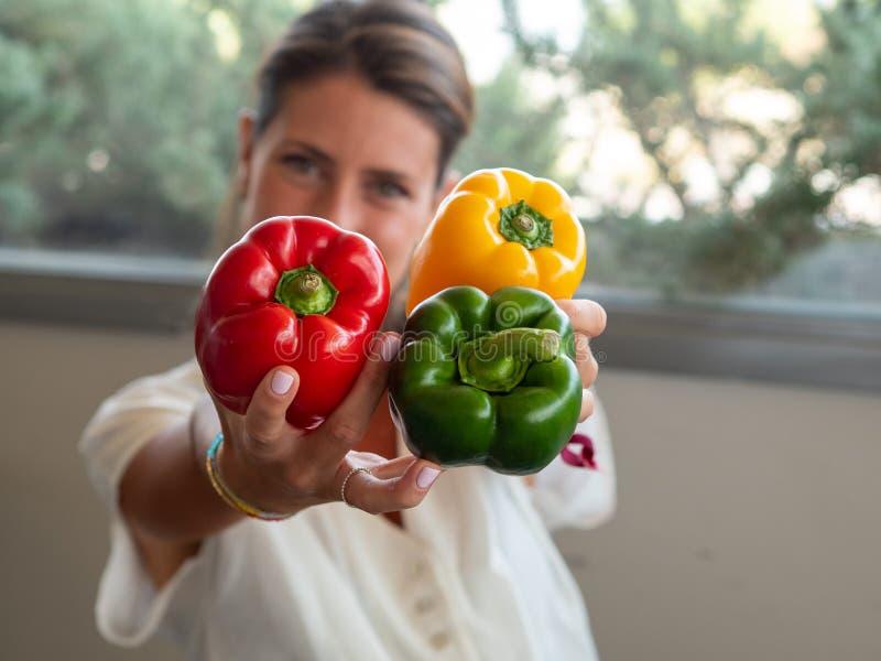 Kaukasische meisjeszitting in haar keuken die drie grote gekleurde peper tonen Groen, rood en geel stock fotografie