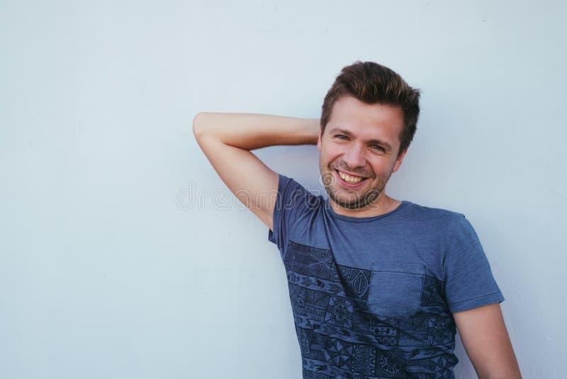 Kaukasische mens in blauw overhemd die dichtbij muur en glimlach zich een weinig bevinden royalty-vrije stock afbeeldingen