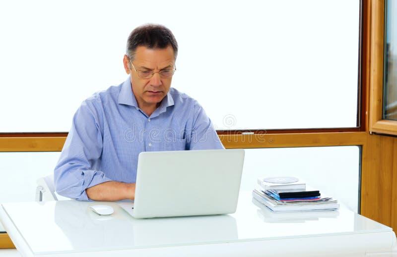 Kaukasische mens die aan zijn laptop computer werken royalty-vrije stock foto's