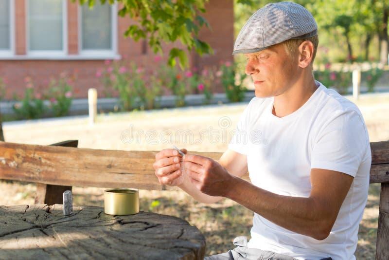 Kaukasische mens die een sigaret in een de zomerdag rollen royalty-vrije stock afbeeldingen