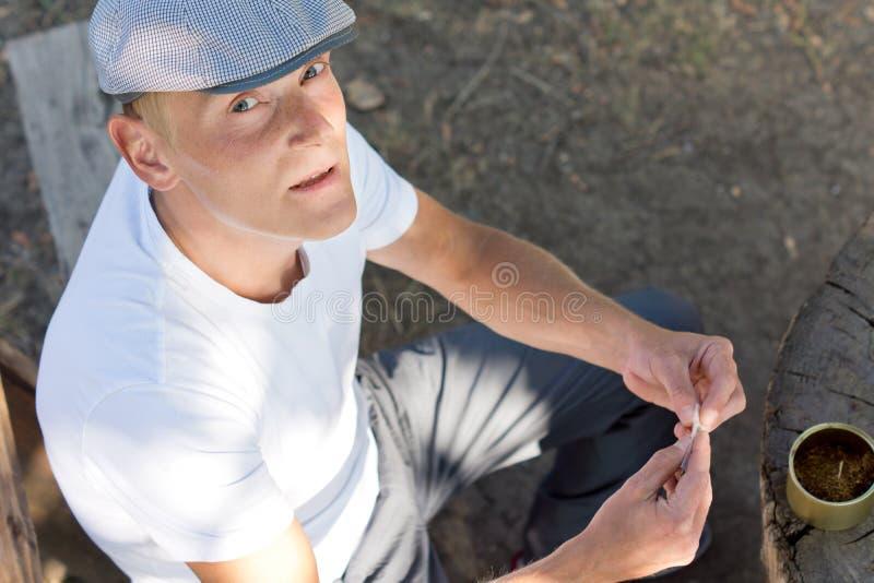 Kaukasische mens die een sigaret in het park rollen royalty-vrije stock fotografie