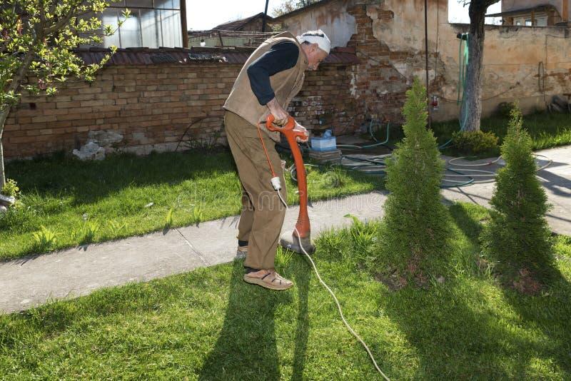 Kaukasische mens die gebruikend borstelsnijder tuinieren De activiteit van de de lentetijd hobby royalty-vrije stock afbeeldingen