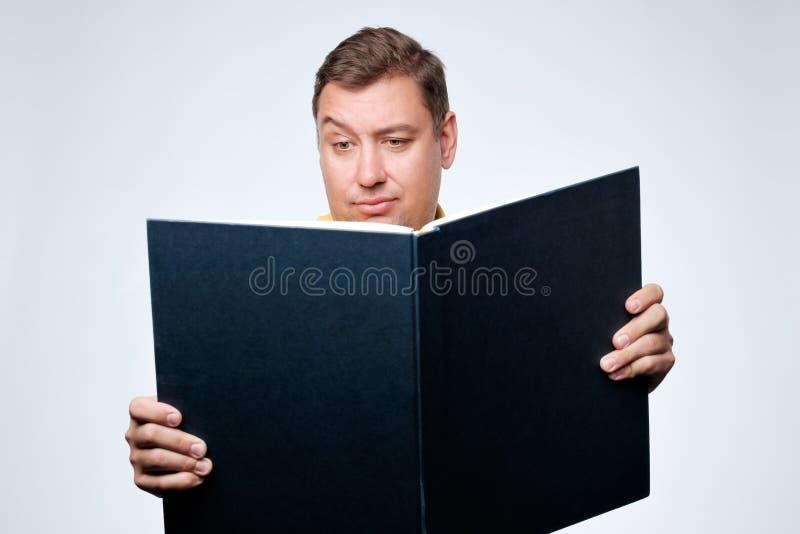 Kaukasische mens die groot boek en met twijfel openen die op zoek naar belangrijke informatie kijken stock afbeelding