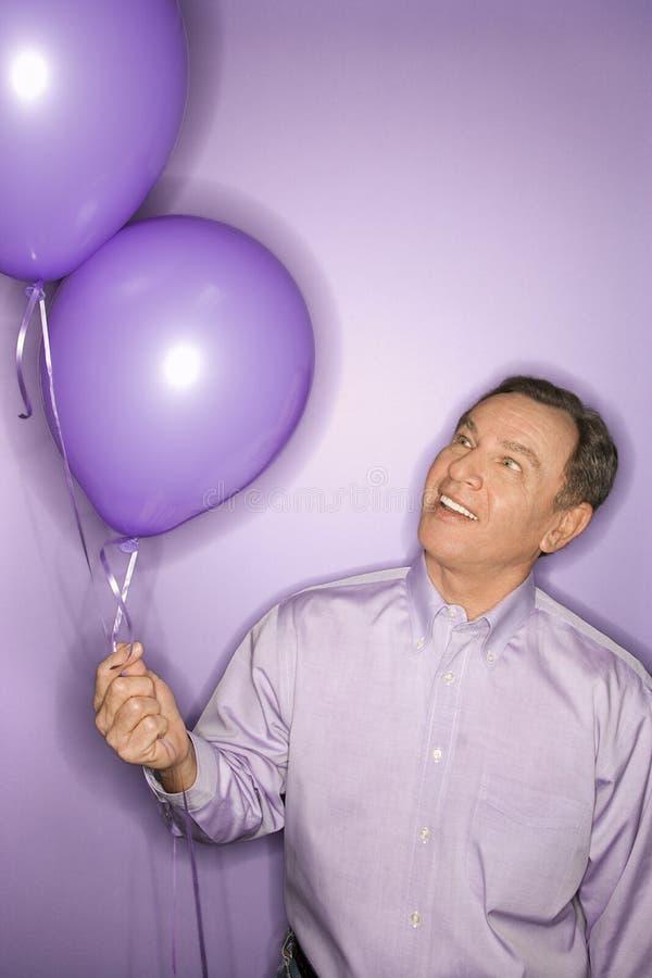 Kaukasische mens die purpere ballons houdt. royalty-vrije stock foto's