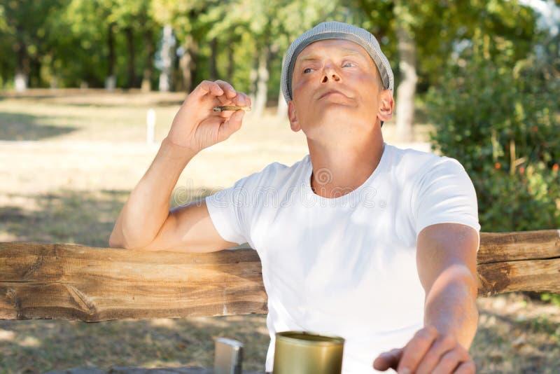 Kaukasische mens die van een gerolde sigaret genieten royalty-vrije stock fotografie