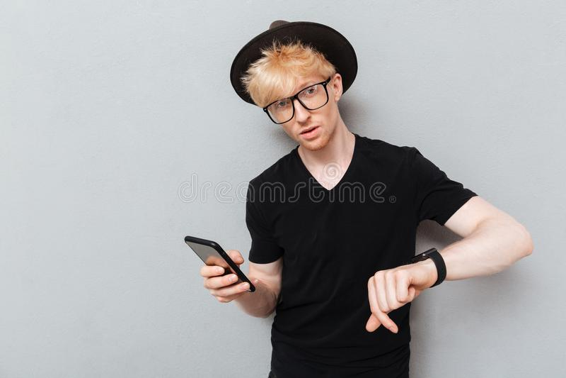 Kaukasische mens die zijn horloge en mobiele telefoon met behulp van royalty-vrije stock afbeelding