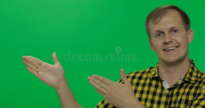 Kaukasische mens in geel overhemd die iets tonen Plaats voor uw embleem of tekst stock foto's