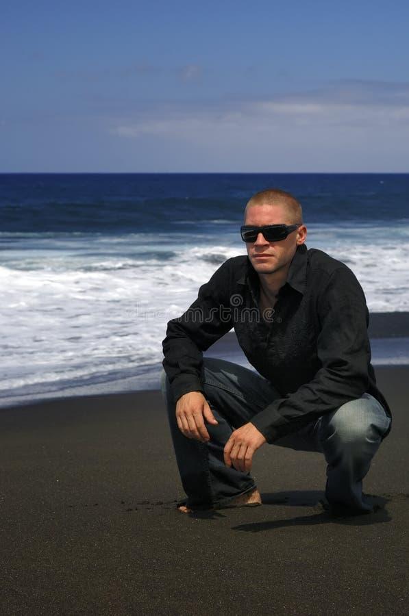 Kaukasische mens met glazen op het strand stock foto