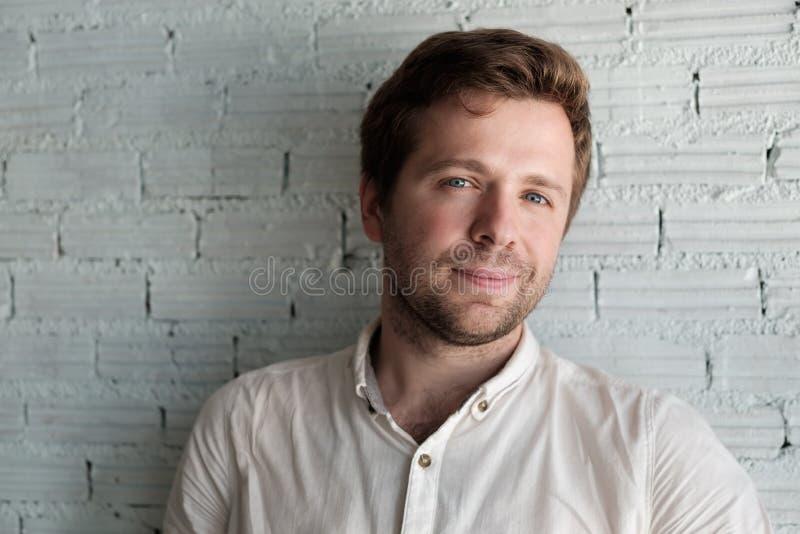 Kaukasische mens in wit overhemd die dichtbij muur en glimlach zich een weinig bevinden Hij is tevreden en zeker stock afbeelding
