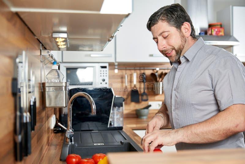 Kaukasische mensen scherpe tomaten in de keuken stock afbeelding