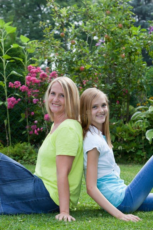 Kaukasische moeder en dochter die in een tuin glimlachen stock fotografie