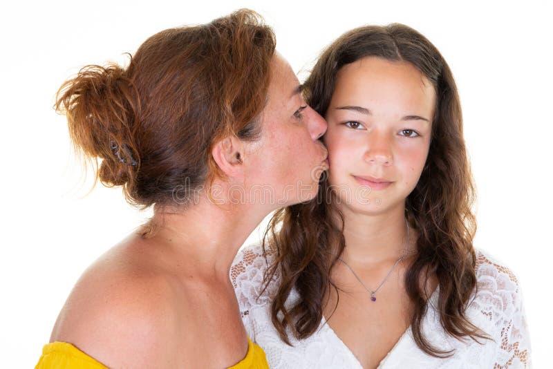 Kaukasische mooie de kuswang van de vrouwen volwassen moeder haar tienerdochtermeisje status geïsoleerd over witte achtergrond royalty-vrije stock afbeeldingen