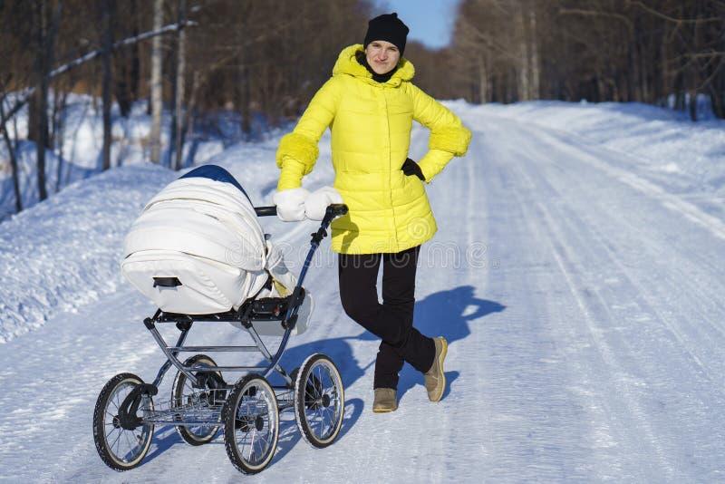 Kaukasische Mutter im gelben Mantel geht mit weißem Kinderwagen auf Schneestraße unter dem Wald am sonnigen Tag des Winters stockfotografie