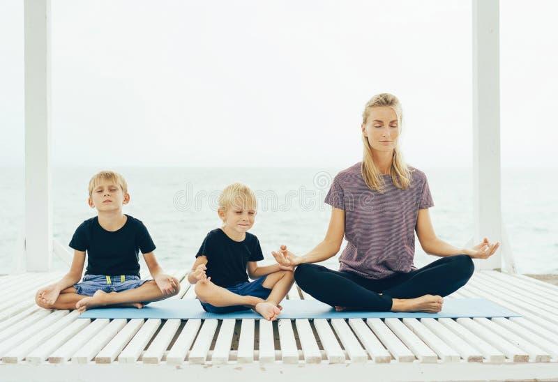 Kaukasische Mutter mit dem Yoga mit zwei Sohnpraxis im Freien lizenzfreie stockbilder