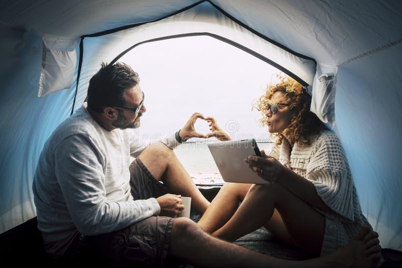Kaukasische Paare in der Liebe innerhalb eines Zeltes auf einem freien Kampieren am Strand, zum des Spaßes in einer anderen Art F stockfotografie