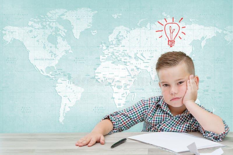 Kaukasische school-age jongen in een plaidoverhemd op de achtergrond van de wereldkaart die over mondiale problemen denken royalty-vrije stock afbeelding